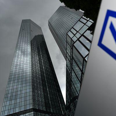 Kaksi pilvenpiirtäjää tummenevan taivaan alla Saksan Frankfurtissa. Etualalalla Deutsche Bankin logo.