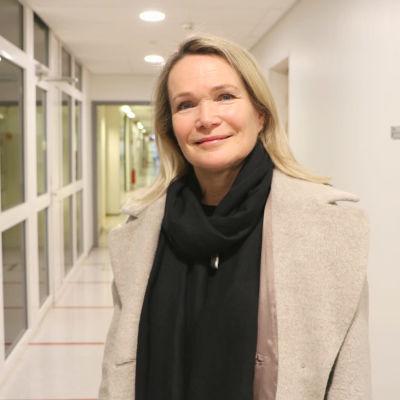 En kvinna med ljust, axellångt hår tittar in i kameran och ler lite. Hon är iklädd ljus kappa och mörk halsduk.