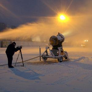 Kuvaaja kuvaa jalustakameralla urheilukentän reunassa lumitykin puhaltamaa lumipilveä aurinkoa vasten