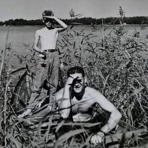Mustavalkoisessa kuvassa 1950-luvulta nuori poika ja mies kaislikossa ilman paitaa