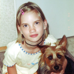 Kandit-ohjelman eläinlääkärikandi Veera pienenä tyttönä koiran vierellä