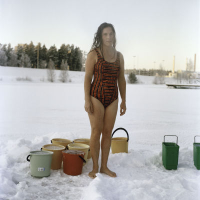 Kvinna på isen i Imatra omgiven av hinkar