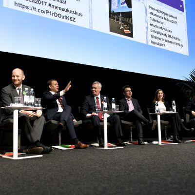 Kahdeksan puoluejohtajaa istuu lavalla messuilla.