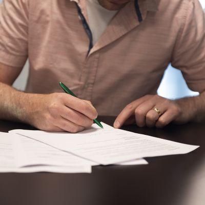 Mies allekirjoittaa työsopimusta.