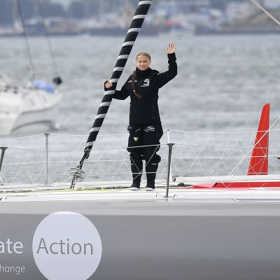Greta Thunberg heiluttaa purjeveneen kannella.