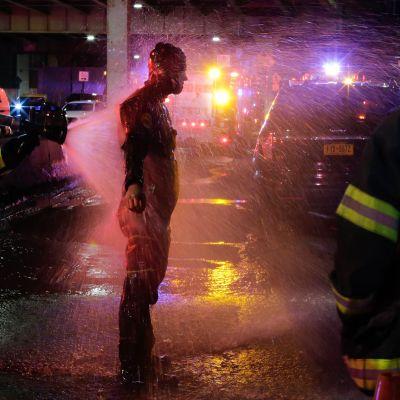 Sukeltajaa suihkutettiin vedellä pelastusoperaation jälkeen New Yorkissa sunnuntaina.