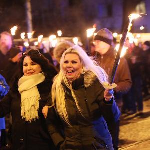 Ihmiset marssivat pimeässä soihtujen kanssa