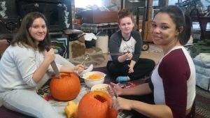 Tre unga kvinnor gör Halloweenprydnader av pumpor