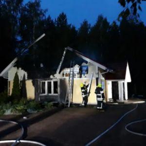 Två brandmän står vid ett förkolnat, ljusgult trähus som förstörts i en brand.