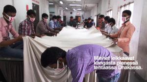 Miehet leikkaavat kangasta pienessä tehtaassa Dhakassa.