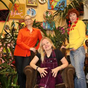 Liksom Lux -yhtyeen jäsenet yhteiskuvassa Rosa Liksomin työhuoneella. Taustalla palmuja ja seinälle ripustettuja maalauksia.