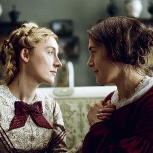 Charlotte (Saoirse Ronan) och Mary Anning (Kate Winslet) sitter mittemot varann och ser varandra djupt i ögonen.