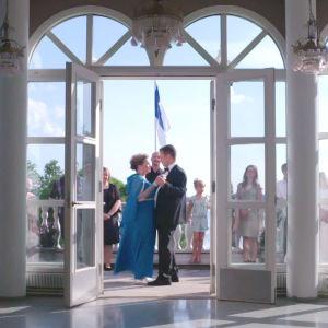 Kuva sisältä salista kohti terassia, jossa nainen ja mies tanssivat juhlaväen keskellä.