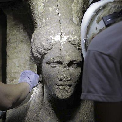 Arkeologeja tutkimassa karyatidin kasvoja.