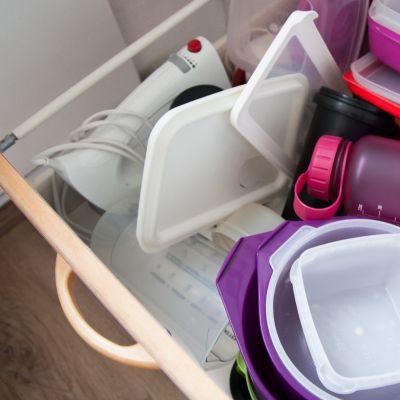 Paljon muoviastioita sikin sokin keittiön vetokaapissa.