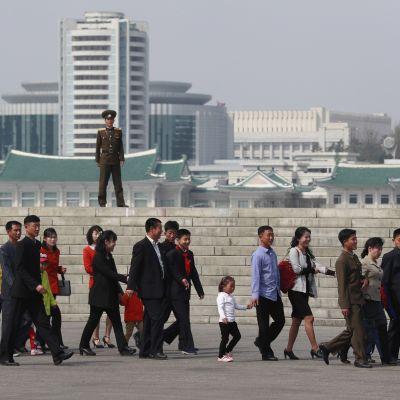 Pohjoiskorealainen sotilas katselee ihmisiä, jotka kävelevät maan perustajan syntymäpäivän vuosipäivää juhlistavaan kukkanäyttelyyn.