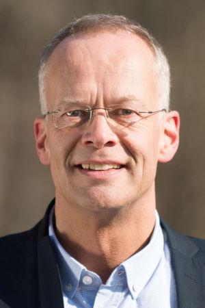 En man i blå skjorta och mörkare blå kavaj med glasögon utan skalmar.