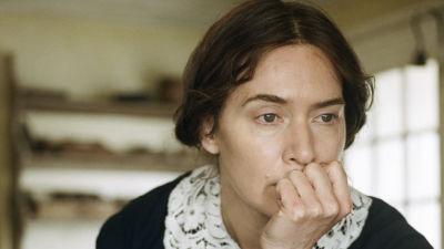 Mary Anning (Kate Winslet) sitter vid ett bord och ser fundersam ut då hon lutar sitt huvud mot handen.
