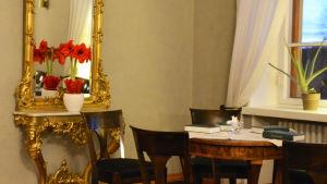 På ett bord framför en spegel står en röd julros. Invid den finns ett bord och stolar. På bordet står två ljusstakar och några psalmböcker.