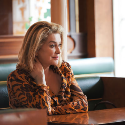 Catherine Deneuve vid ett cafébord.