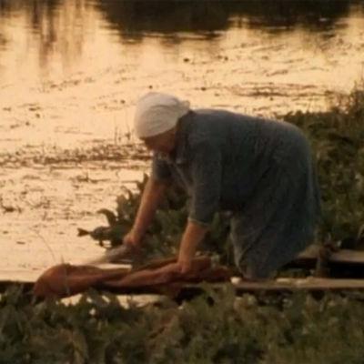 Nainen pesee pyykkiä rannassa dokumentissa Kaukaiset karjalaiset
