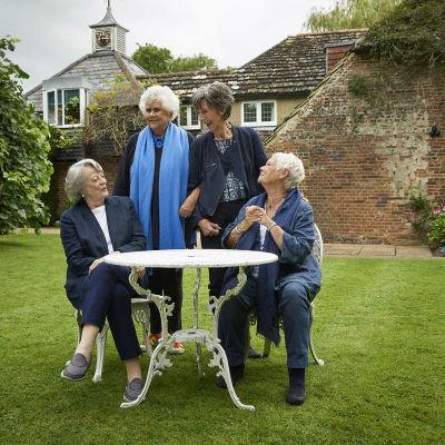 Fyra glada damer i samspråk i  Joan Plowrights trädgård.