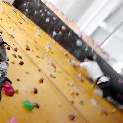 Mies kiipeää kiipeilyseinällä Jyväskylässä.