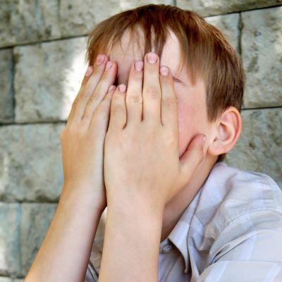 Poika istuu maassa kasvot käsiin haudattuna.