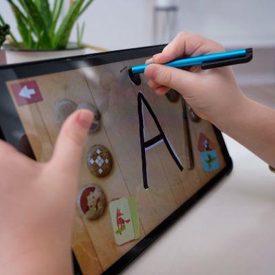 Esikoululainen harjoittelee kirjainten kirjoittamista Molla ABC mobiilisovelluksen avulla.