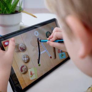En förskolepojke övar sig på att skriva bokstäver i en applikation på en pekplatta.