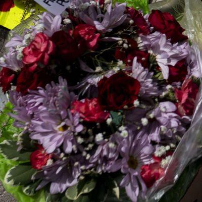 Blommor ligger på marken bredvid en bild av George Floyd.