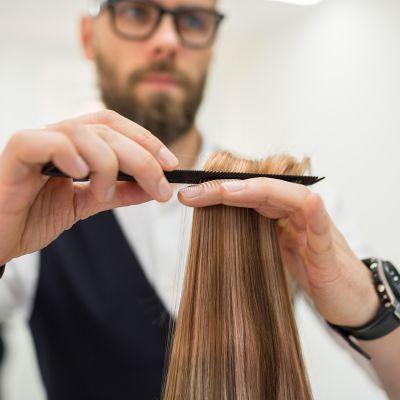 mies leikkaa pitkiä hiuksia