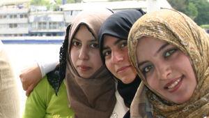 Huivipäiset, hymyilevät egyptiläistytöt Niilin risteilyllä.