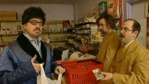 Kyläkaupassa tarkkaavaisia myyjiä ja vaivaantuneita asiakkaita.