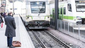 Resenärer väntar på tåget.