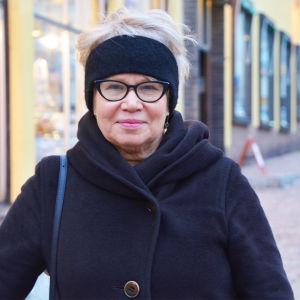 En medelålders kvinna i svart kappa och svart pannband står utanför ett gult hus i Gamla stan i Borgå. Hon tittar in i kameran och ler lite.