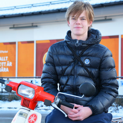En tonårskille sitter på en röd skoter eller moped utanför en matbutik. Han tittar in i kameran och ler.