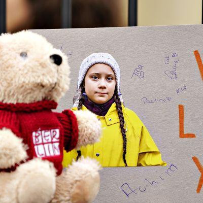 """Pahviin on kiinnitetty ruotsalaisen Greta Thunbergin kuva ja """"Me rakastamme sinua"""" -teksti. Pahvin edessä on ruskea nallekarhu."""