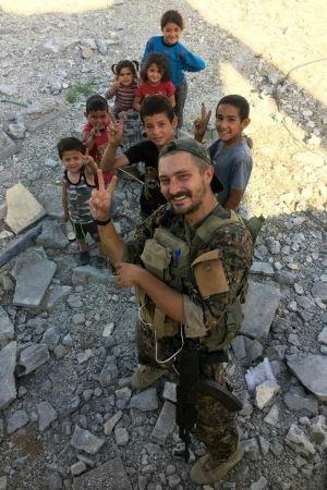 """Den finska frivilligsoldaten """"Bagok Kullervo"""" med en grupp barn utanför Raqqa."""