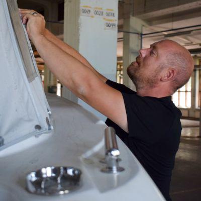 Ben Lindström sätter fast presenning på båt.