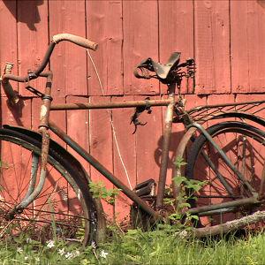Vanha ruostunut polkupyörä nojaa punaista ladonseinää vasten.