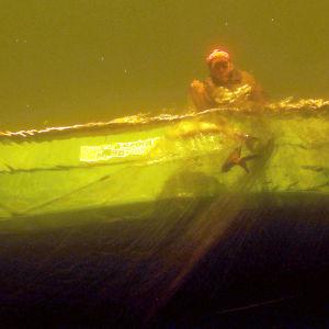 Kalastaja nostaa verkkoja, kuvattu vedestä.