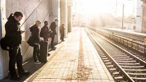 Folk står och väntar på tåget.