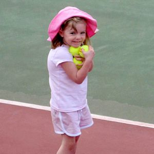 En liten flicka står på en tennisplan med tennisbollar i famnen. Hon är klädd helt i ljusrött med en ljusröd hatt på huvudet.