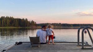 Man och barn på brygga ser på solnedgång.