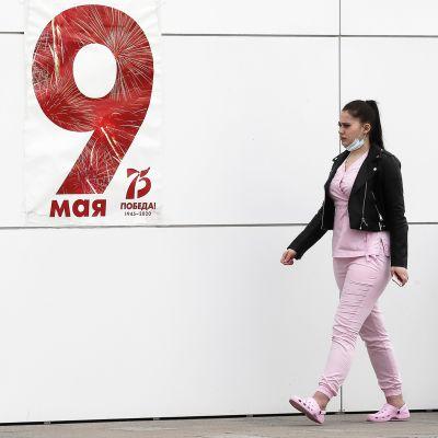 Kommunarka-sairaalan työntekijä kevelee sairaalan ulkoseinään ripustetun voitonpäivän julisteen ohi.