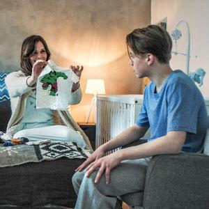 Nainen, mies sekä nuori mies ja nainen istuvat sängyllä katsellen lastenvaatteita.