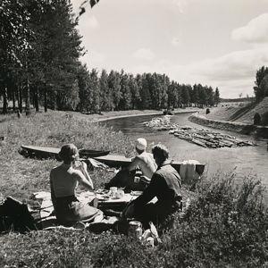Mustavalkoinen kuva: Kolme henkilöä piknikillä kanavan rannalla, kanavassa uitetaan tukkeja.