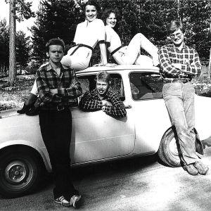 Auton katolla istuu kaksi nuorta naista, kuskin paikalla nuori mies katsoo ikkunasta ulos ja kaksi miestä seisoo autoon nojaillen.