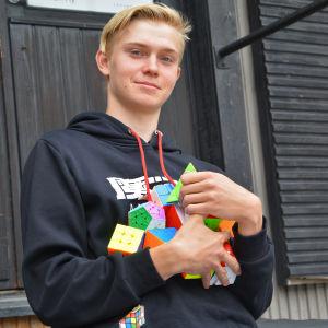 Närbild på en tonårig pojke utanför ett svart trähus. Pojken håller en massa färggranna Rubiks kuber i sin famn och tittar in i kameran.